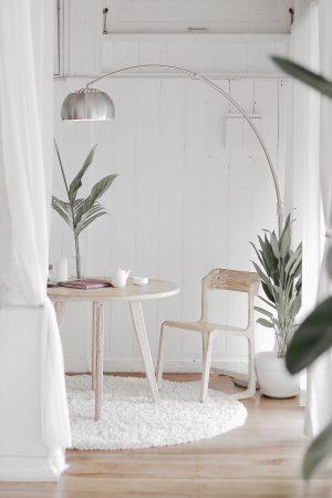 Salon dans des tons clairs et apaisants avec table, chaise et planntes vertes