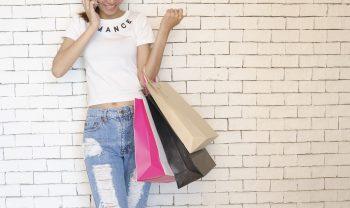 Femme avec des sacs de shopping devant un mur en briques blanches